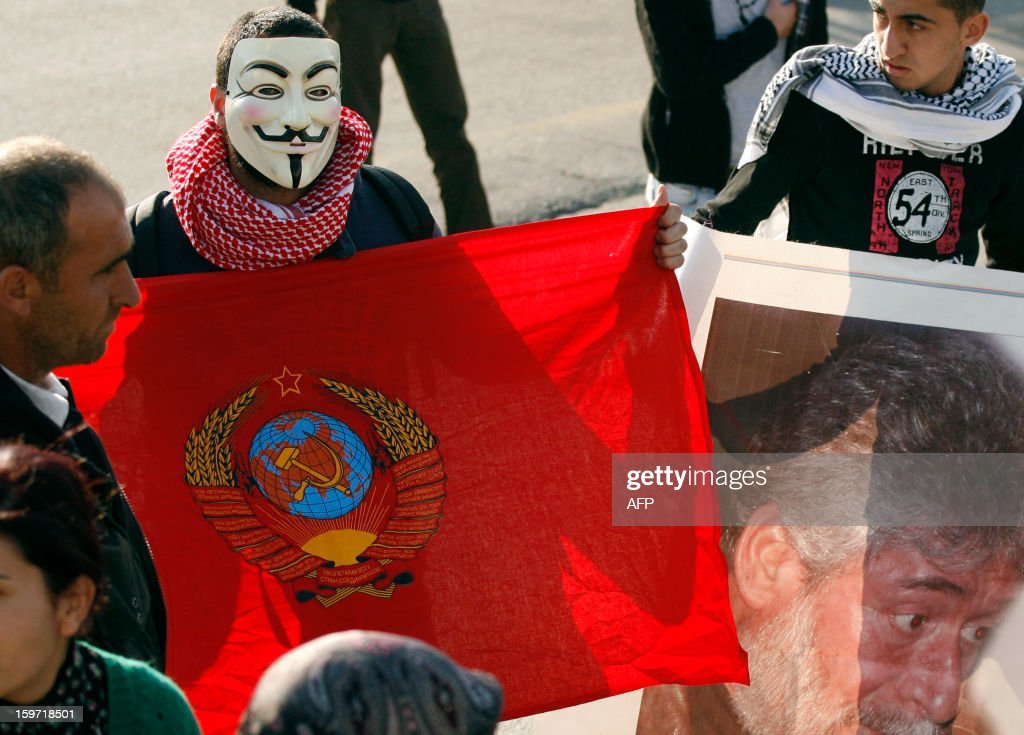 A protestor wearing a mask of the anonymous movement holds a flag near a poster featuring Georges Abdallah during a demonstration to call for his release outside the United Nations Interim Force in Lebanon (UNIFIL) French base on January 19, 2013 in the southern city of Deir Kifa. Georges Ibrahim Abdallah was sentenced to life imprisonment in France in 1984 for his part in the 1982 murders of two diplomats, Charles Robert Day, an American and Yacov Barsimantov, an Israeli, in Paris.