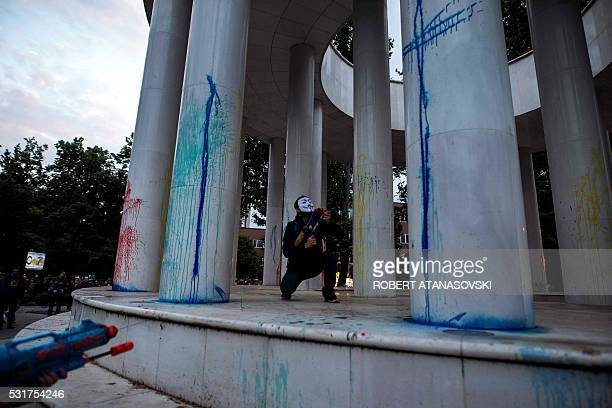 TOPSHOT A protestor wearing a mask uses a water gun to spray colored paint on marble columns of a monument during an antigovernment protest in Skopje...