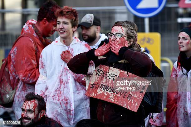 A protestor wearing a protective suit covered in fakeblood gestures before a police barricade before the start of the EUCanada summit to conclude the...