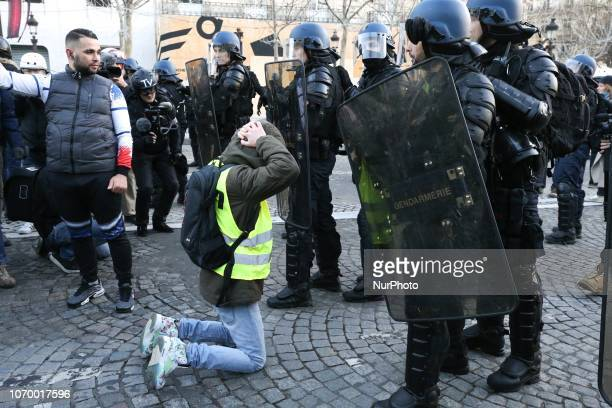 A protestor wearing a quotyellow vestquot gets down in front riot police officers on the Champs Elysees avenue during a demonstration against rising...