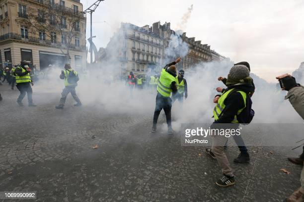 A protestor wearing a quotyellow vestquot sends back a tear gas canister during clashes with riot police on the Champs Elysees avenue during a...