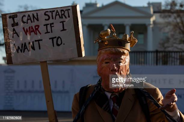 Protestor wearing a stylized mask of President Donald Trump holds up a sign outside of the White House on January 8, 2020 in Washington, DC....