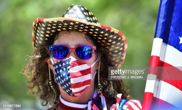 TOPSHOT A protestor wearing a US flag mask demands the Stay at Home order to be lifted and the government to reopen the state during an Open...
