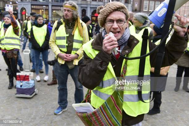 A protestor wearing a yellow vest shouts slogans in a microphone during a demonstration in Amsterdam the Netherlands on December 15 2018 The socalled...