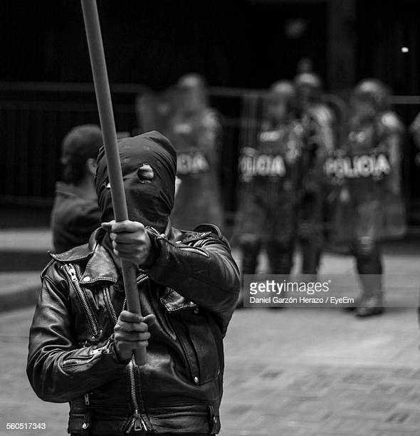 protestor wearing mask while holding nightstick - protestor mask stock pictures, royalty-free photos & images