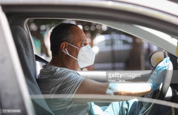 Protestor wears a face mask and gloves as Uber and Lyft drivers with Rideshare Drivers United and the Transport Workers Union of America conduct a...