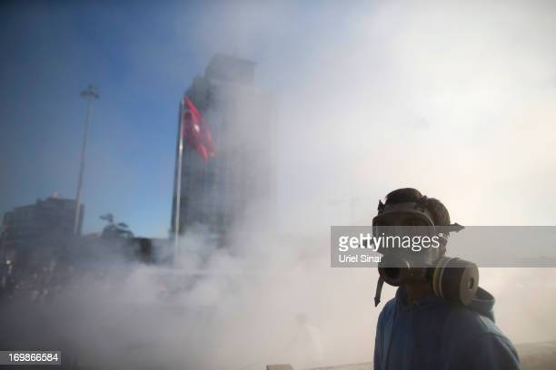 Protestor wears a gas mask after a car was burned at Taksim square on June 3 2013 in Istanbul Turkey The protests began initially over the fate of...