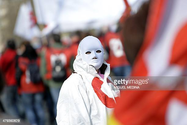 A protestor wears a mask as people demonstrate for wages employment job security and against the proposed 'pact of responsibility' during a protest...