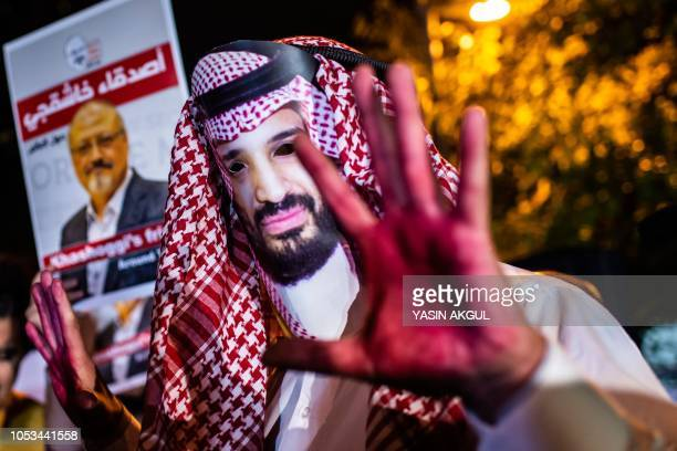 A protestor wears a mask of depicting Saudi Crown Prince Mohammad Bin Salman with red painted hands next to people holding posters of Saudi...