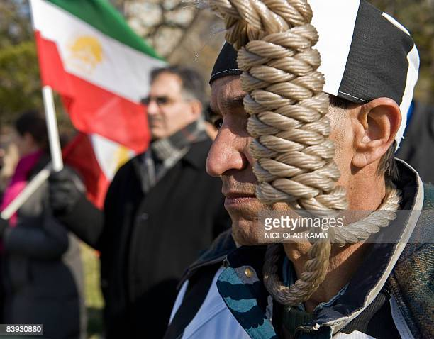 A protestor wears a noose as another waves an Iranian flag during a demonstration to demand the continued US protection of 3500 members of Iran's...