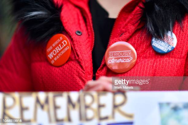 A protestor wears a pin stating SERIOUSLY AMERICA while demonstrating with Philadelphia Airport TSA and airport workers outside the Philadelphia...