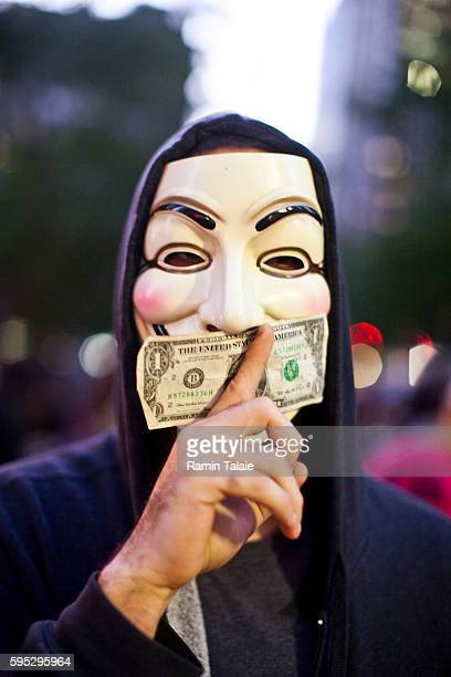 A protestor wears an anonymous mask holds a dollar bill to his mouth at Zuccotti Park during a demonstration in New York City on Saturday October 8...