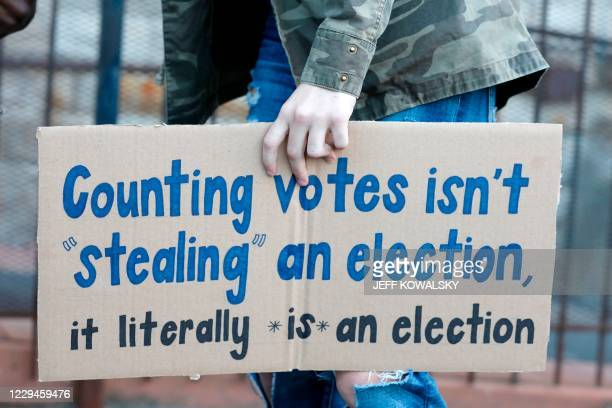 Protestor who wants every vote counted from the 2020 presidential election, carries a sign as they march down Woodward Avenue on November 4, 2020 in...