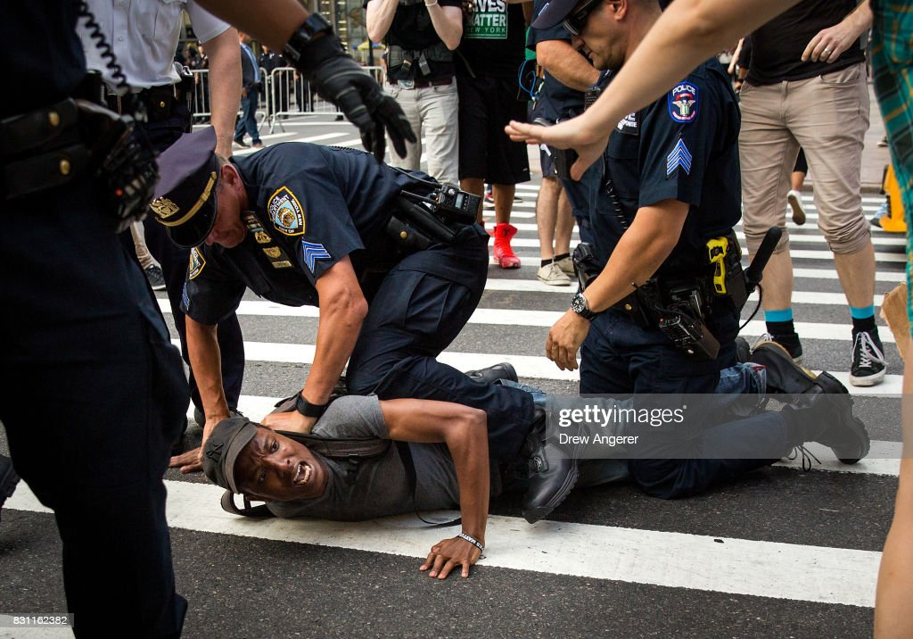 A protestor, who was marching on 5th Avenue against white supremacy and racism, is held on the ground while being arrested by New York City Police (NYPD) officers, August 13, 2017 in New York City. 32-year-old Heather Heyer was killed in Charlottesville on Saturday when a car driven by a white supremacist barreled into a crowd of counter-protesters following violence at the Unite the Right rally.