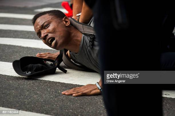 A protestor who was marching on 5th Avenue against white supremacy and racism is held on the ground while being arrested by New York City Police...
