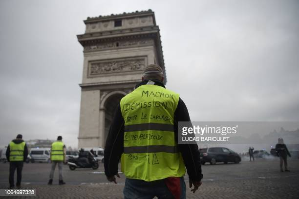 TOPSHOT A protestor with a yellow vest reading Macron resignation stands in front of the Arc de Triomphe on the Champs Elysees in Paris on November...