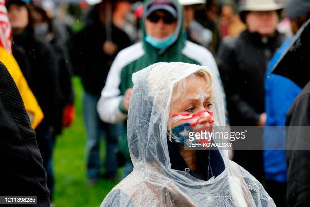 A protestor with an upside down flag painted on her face stands at an American Patriot Rally organized by Michigan United for Liberty protest for the...