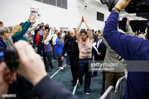 A protestor with 'Eminent Domain This' written on his chest is escorted out as Republican presidential candidate Donald Trump speaks during a rally...