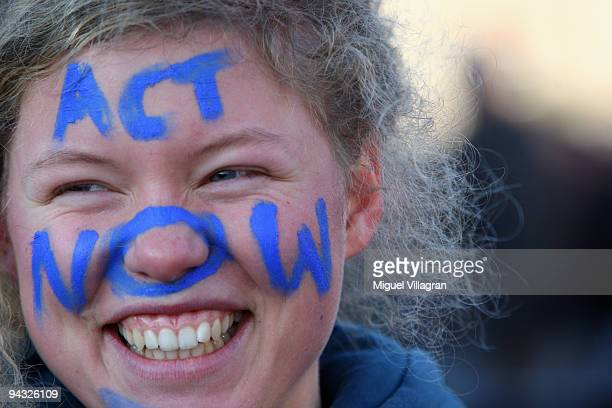 A protestor with the writing 'Act now' on her face takes part in a protest march towards the United Nations Climate Change Conference 2009 at the...