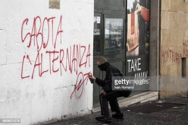 Protestor writes on a wall near a McDonald's the phrase 'Sabota l'Alternanza' during the demonstration in the streets of Naples against the...