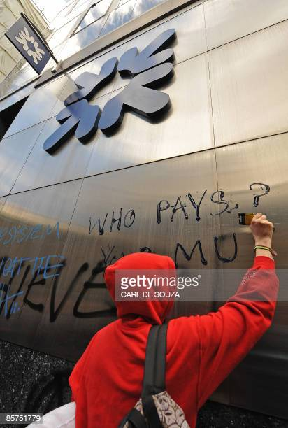 Protestor writes the words 'Who Pays' on the wall of Royal Bank Scotland branch, in London, on April 1, 2009. Leaders wrangled Wednesday on how a G20...