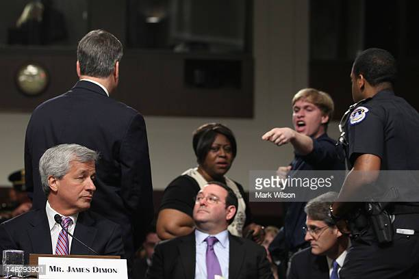 A protestor yells at President and CEO of JPMorgan Chase Co Jamie Dimon as he appears before a Senate Banking Committee hearing on Capitol Hill June...