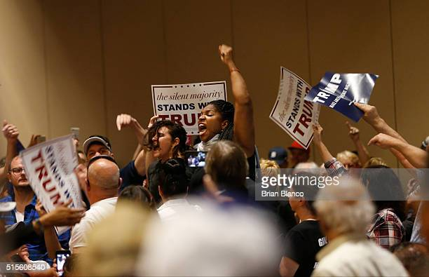 Protestors are removed from the Tampa Convention Center as Republican presidential candidate Donald Trump speaks to supporters during a town hall...