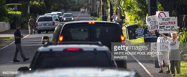 Protestors are seen holding signs as US President Barack Obama's motorcade returns to his vacation compound at Kailuana Place upon returning from a...
