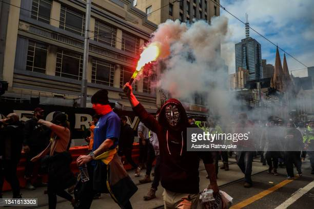 Protestors are seen marching as a flare is lit as thousands march through Melbourne after State Government announces construction shutdown on...