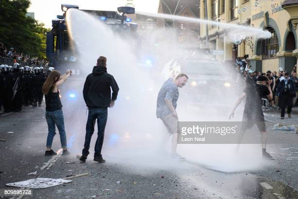 Protestors are sprayed by police water cannons during the 'Welcome to Hell' anti-G20 protest march on July 6, 2017 in Hamburg, Germany. Leaders of...