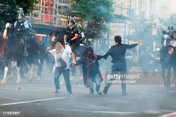 TOPSHOT Protestors are tear gassed as the police disperse them near the White House on June 1 2020 as demonstrations against George Floyd's death...