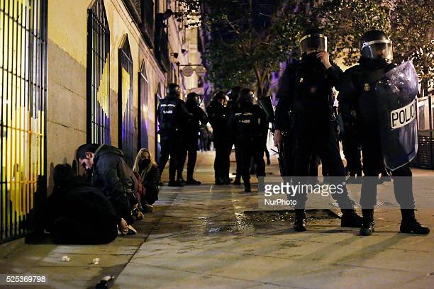 Protestors arrested wait on their knees handcuffed to be transferred to the police station during a protest against the 'Clamp law' in Madrid Spain...