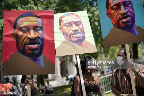 Protestors at Foley Square hold images of George Floyd during a Juneteenth rally in New York on June 19, 2020. - The US marks the end of slavery by...