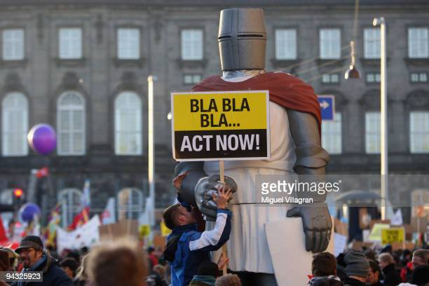 Protestors attach a sign reading 'Bla Bla Bla Act Now' on a figure of a knight before marching towards the United Nations Climate Change Conference...