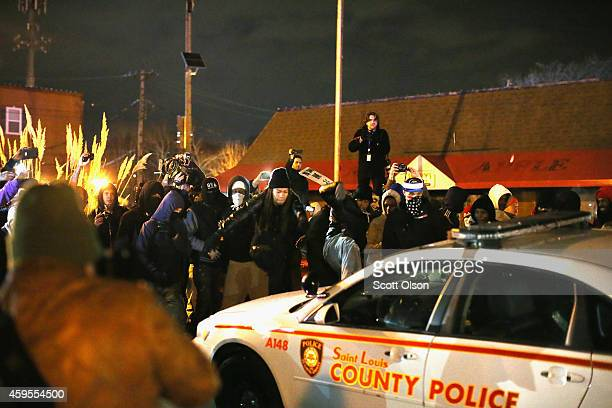 Protestors attack a squad car when riioting broke out following the grand jury announcement in the Michael Brown case on November 24 2014 in Ferguson...
