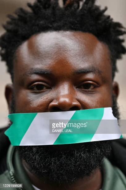 Protestors attend a demonstration outside the Nigerian High Commission against police brutality in Lagos in London on October 21, 2020. - UN...