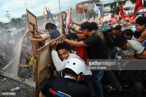 Protestors barricade themselves against water cannon spray during President Benigno Aquino's annual State of the Nation Address on July 28, 2014 in...