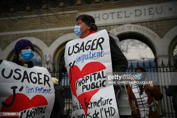 Protestors bear signs reading 'I love public hospital' and 'Austerity kills' during a demonstration against Hotel Dieu's emergencies services closure...