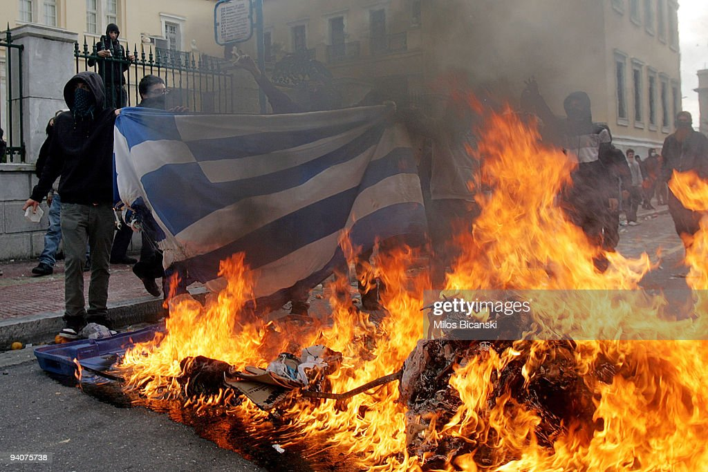 Protestors burn a Greek flag during a demonstration commemorating the fatal shooting of 15-year-old Alexandros Grigoropoulos by police a year ago, on December 6, 2009 in central Athens, Greece. Two police officers will go on trial in the new year for the murder of Grigoropoulos.
