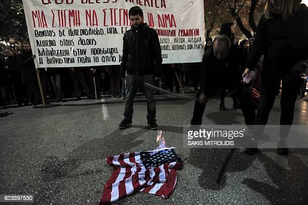 Protestors burn a US flag during a demonstration against the visit of the US president in Thessaloniki on November 15 2016 US President Barack Obama...