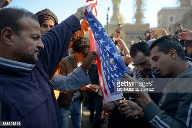 Protestors burn an American flag during a demonstration against US President Donald Trump's decision to recognize Jerusalem as the capital of Israel...