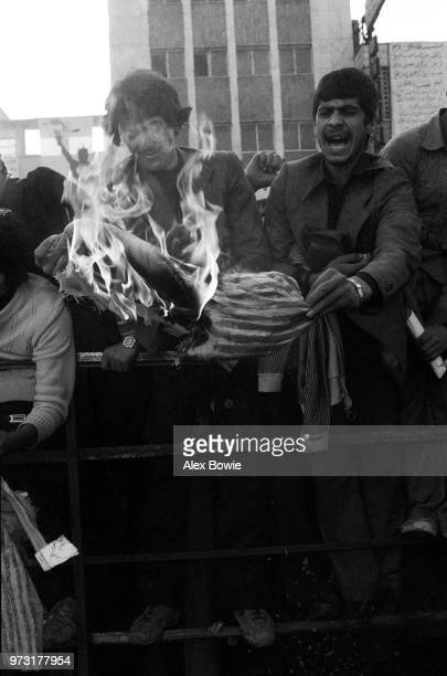 Protestors burn an effigy of Uncle Sam in anger against the United States government outside the former US embassy building where Iranian students...