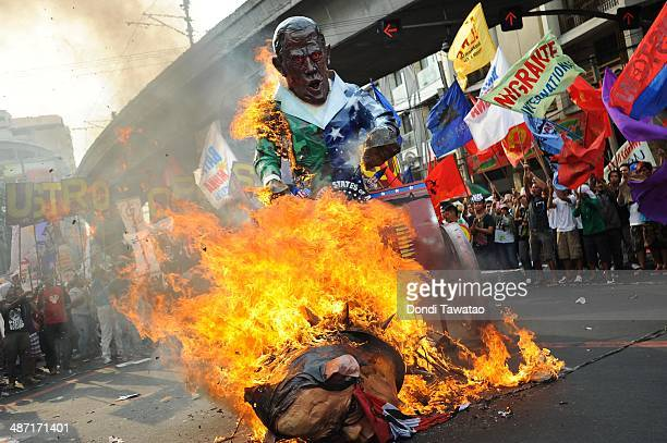Protestors burn an effigy of US president Barack Obama march during a rally to protest against his State visit on April 28 2014 in Manila Philippines...
