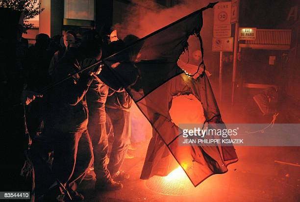 Protestors burn the French and European flags in the streets of the central France city of Vichy during a demonstration against a conference...