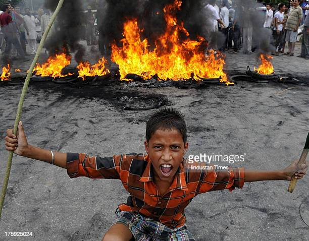 Protestors burn tyres and shouting slogans against the state goverment and Jammu Kashmir Police during a protest on August 10 2013 in Jammu India A...