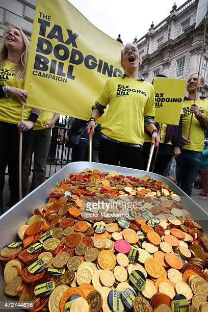 Protestors calling for a bill to stop tax dodging stand outside Downing Street with a wheelbarrow full of chocolate money on May 9 2015 in London...