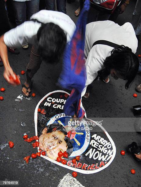 Protestors calling for resignation of President Gloria Arroyo step on her portrait and that of her husband Jose Miguel Arroyo during a rally outside...