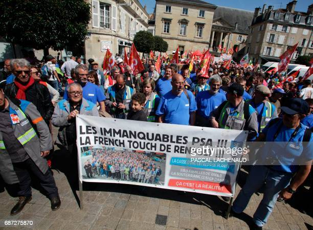 "Protestors carry a banner reading ""The unmissable PSA! Renault's french touch!"" during a demonstration against the decision to fire 250 employees of..."