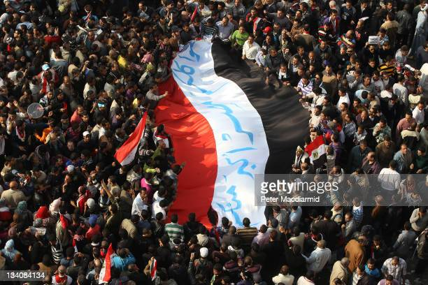 Protestors carry a giant Egyptian flag in Tahrir Square during a mass rally on November 25 2011 in Cairo Egypt Thousands of Egyptians are continuing...