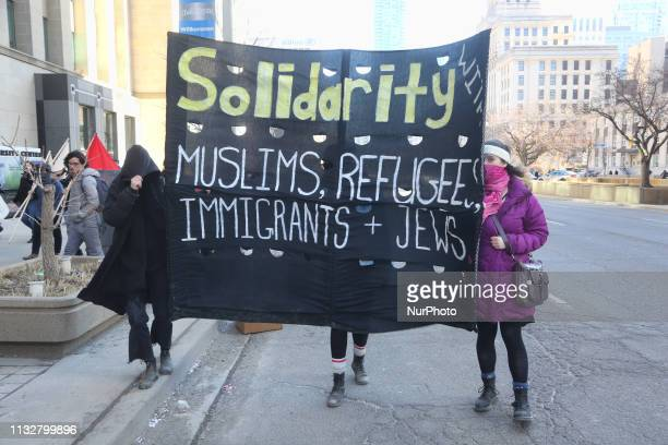 Protestors carry a large banner during a ProMuslim and AntiMuslim rally held in Toronto Ontario Canada on March 23 2019 Counter protesters completely...